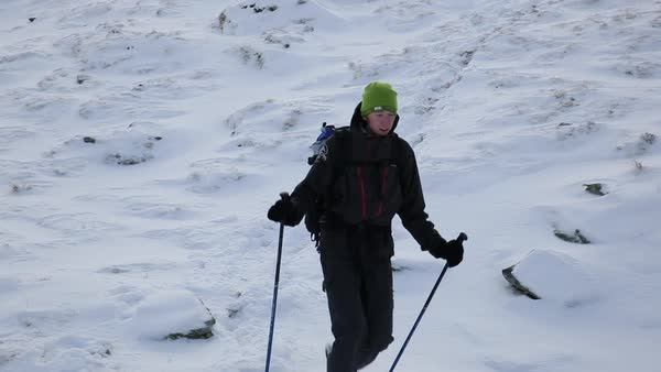 Hand-held shot of a male hiker descending a snow covered slope Royalty-free stock video