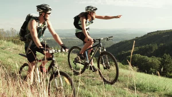 Wide shot of two cyclists on grassy hillside Royalty-free stock video