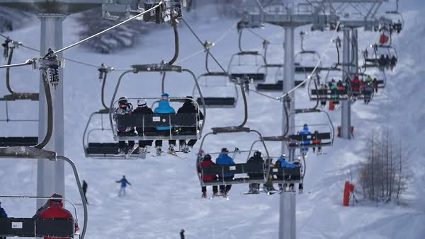 Medium shot of a ski lift transporting skiers up a hill Royalty-free stock video
