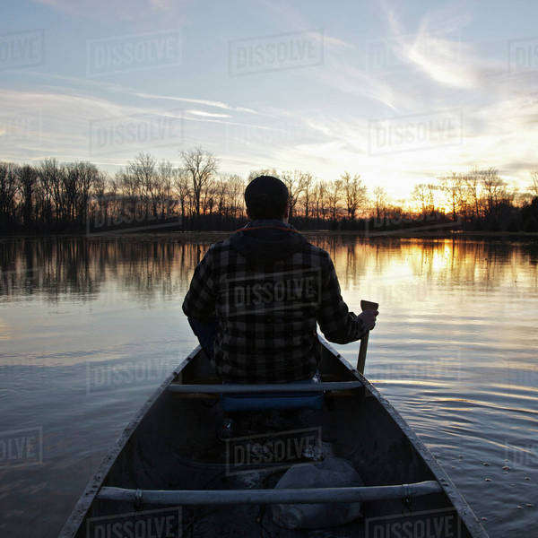 A man in a canoe on a lake at sunset, rear view Royalty-free stock photo