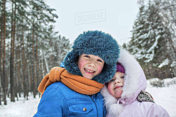 A cheerful brother and sister in warm winter clothing outdoors in winter Royalty-free stock photo