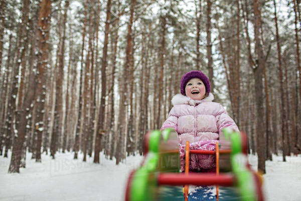 A young cheerful girl on a piece of playground equipment in winter Royalty-free stock photo