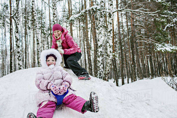 A young girl sledding while her mother looks on Royalty-free stock photo