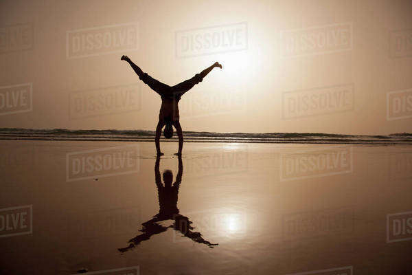 Full length of silhouette man performing handstand at beach Royalty-free stock photo