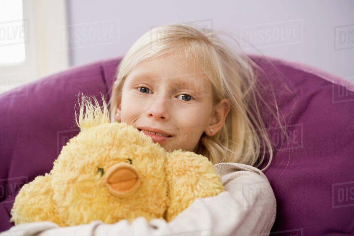 A Young Girl Sitting In A Papasan Chair Hugging A Stuffed Bird