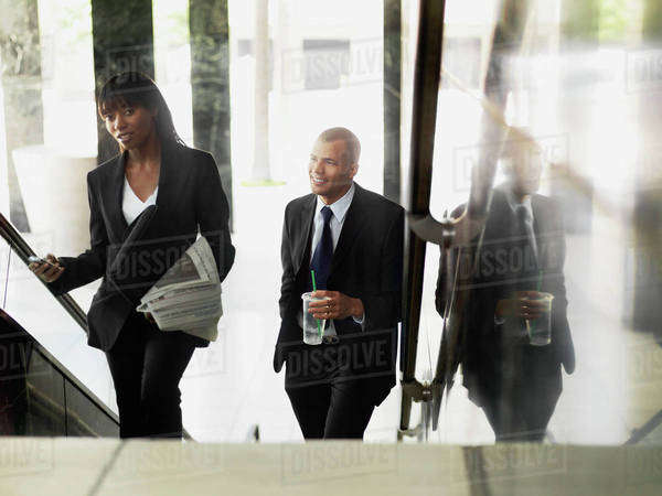 A businesswoman and businessman walking up stairs Royalty-free stock photo