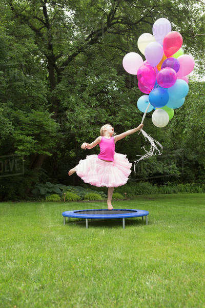 Playful girl jumping on trampoline while holding balloons at backyard Royalty-free stock photo