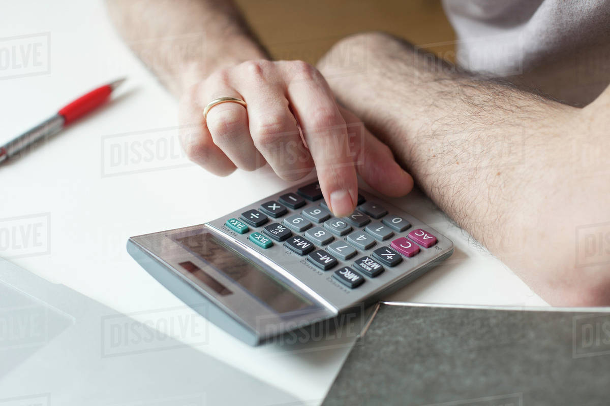 cropped image of man using calculator at table stock photo dissolve
