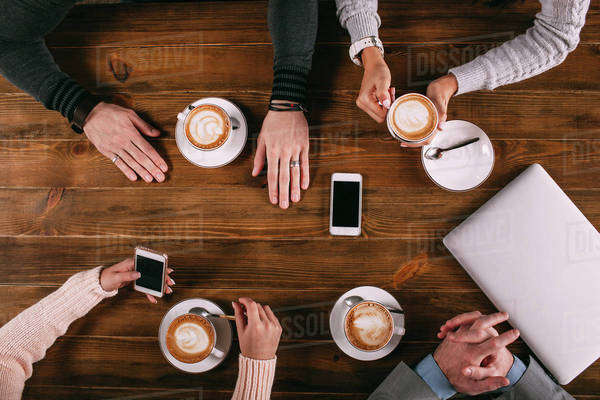 Directly above shot of friends having coffee at wooden table in cafe Royalty-free stock photo