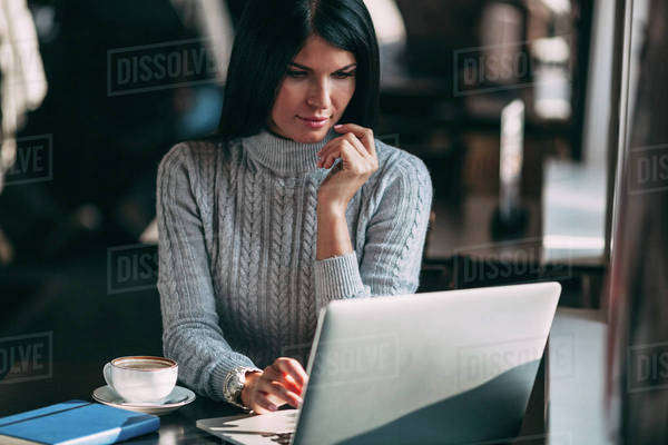 Young businesswoman using laptop at table in cafe Royalty-free stock photo