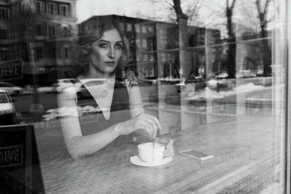Thoughtful young woman stirring coffee in coffee shop Royalty-free stock photo