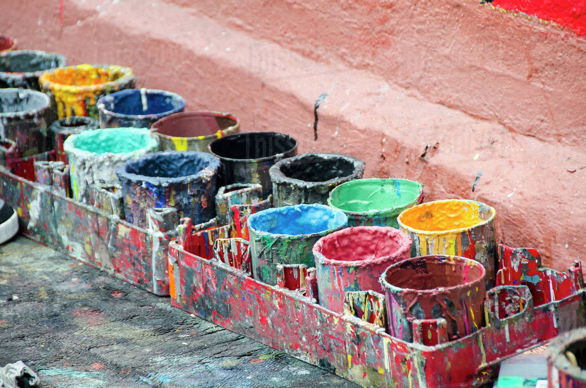 high angle view of colorful paint cans by wall stock photo dissolve