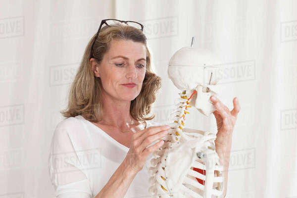 Confident female doctor looking at skeleton while standing in clinic Royalty-free stock photo