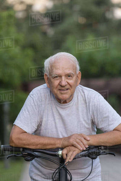 Portrait of senior man leaning on bicycle at park Royalty-free stock photo