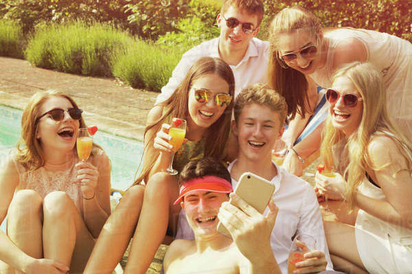 Cheerful friends taking selfie while relaxing by poolside on sunny day Royalty-free stock photo