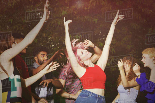 Excited woman dancing with friends at yard during party Royalty-free stock photo