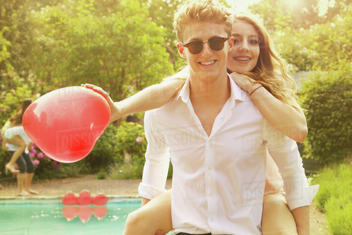 Portrait of happy man piggybacking woman holding heart shape balloon at poolside Royalty-free stock photo