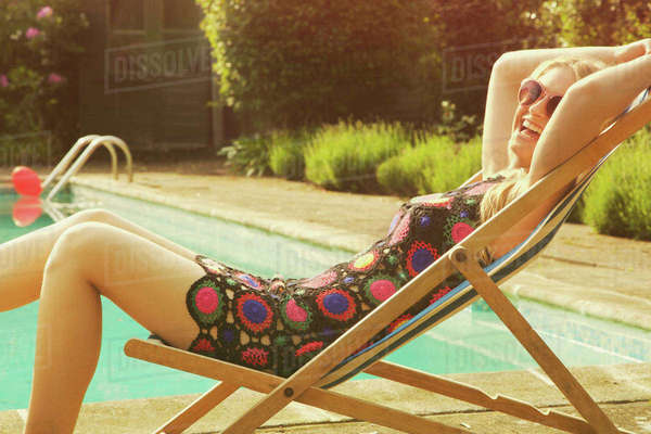 Side view portrait of cheerful woman relaxing on deck chair at poolside Royalty-free stock photo