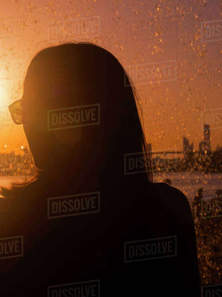 Woman wearing sunglasses standing against splashing water during sunset Royalty-free stock photo