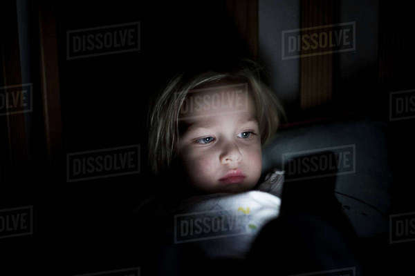 Young boy using mobile phone while lying on bed at night Royalty-free stock photo