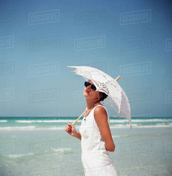 Portrait of a woman holding a parasol and standing on a beach Royalty-free stock photo