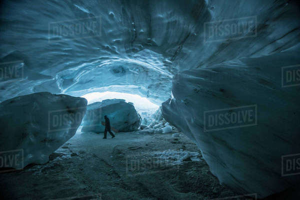 A man carrying snowboard while walking in ice cave, Whistler, British Columbia, Canada Royalty-free stock photo