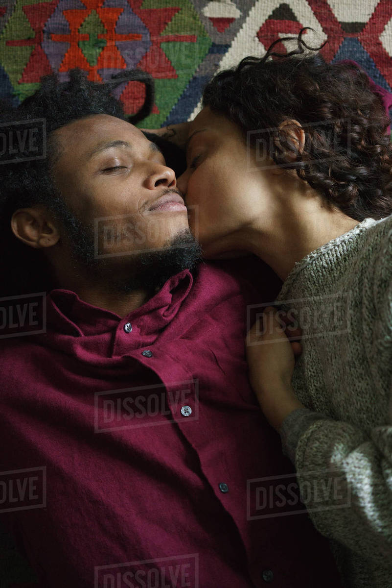 Directly above shot of woman kissing man while lying on carpet Royalty-free stock photo