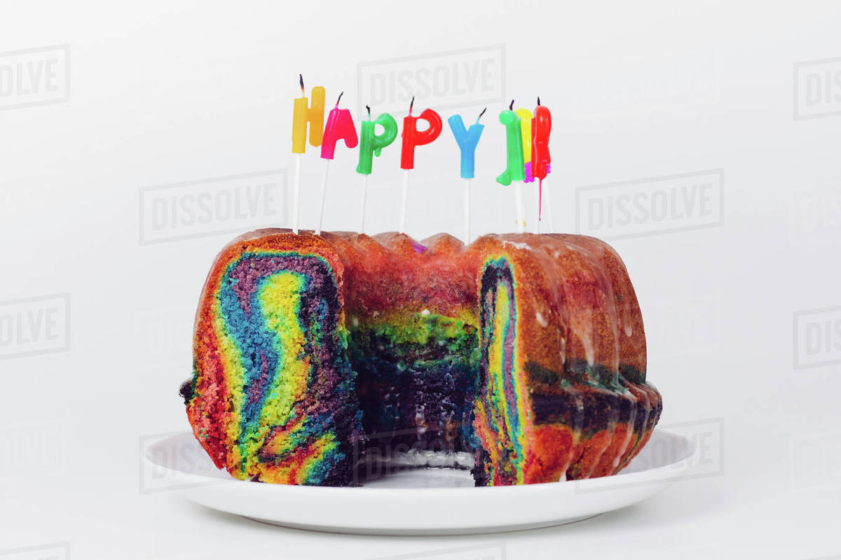 Close Up Of Birthday Candles On Rainbow Cake In Plate Against White Background Royalty
