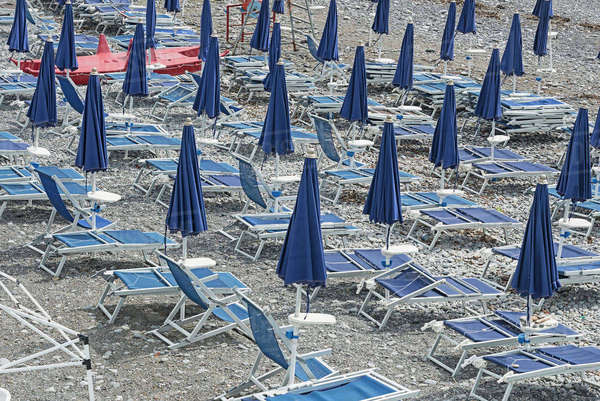 Closed blue parasols and lounge chairs on beach Royalty-free stock photo