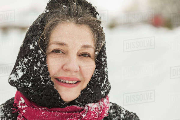 Portrait of smiling senior woman in winter wear covered with snow Royalty-free stock photo