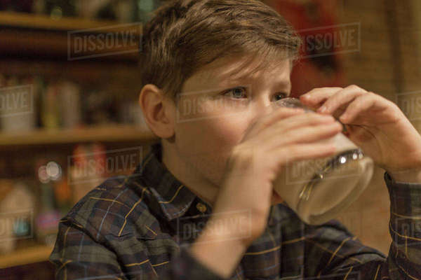 Boy looking away while drinking milk at home Royalty-free stock photo