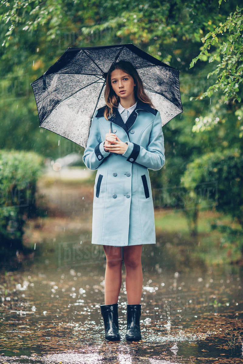 Portrait of teenage girl holding umbrella while standing ...