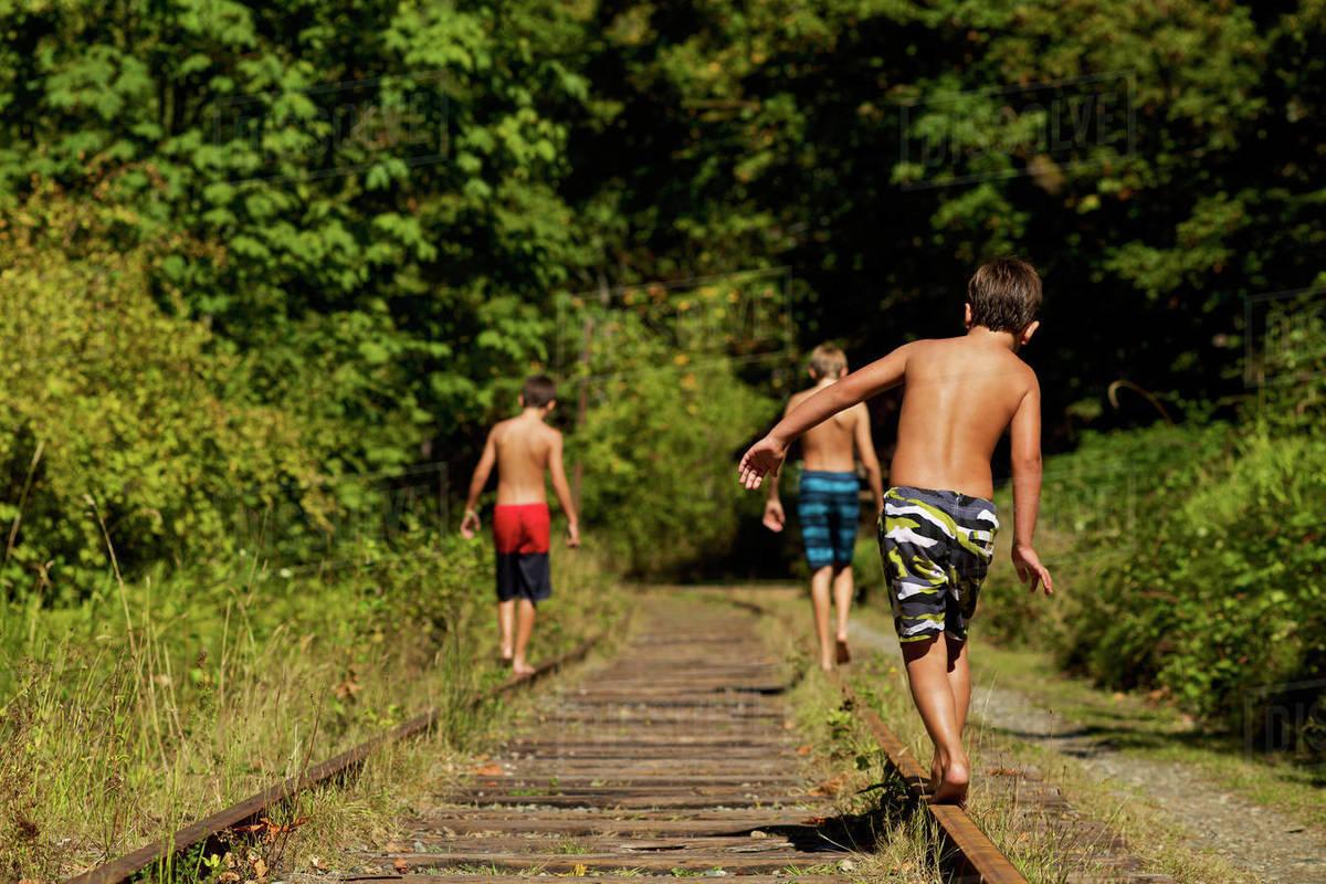 Boys in swim trunks walking along sunny railroad tracks in woods Royalty-free stock photo