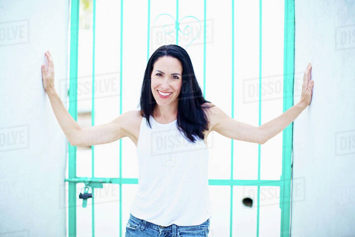 Portrait confident, smiling woman standing in front of turquoise summer gate Royalty-free stock photo