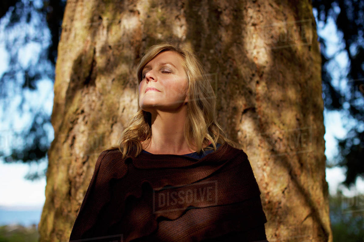 Portrait serene woman with eyes closed standing at sunny tree trunk Royalty-free stock photo