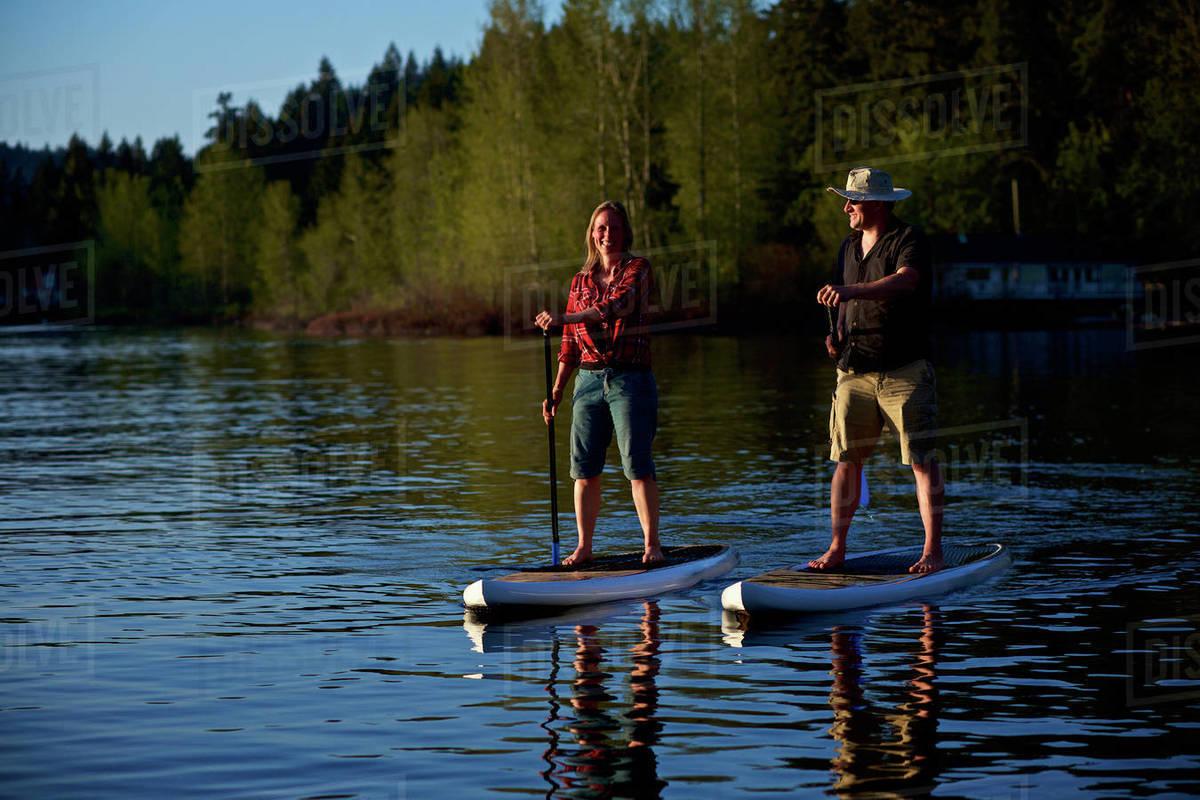 Couple standup paddleboarding on sunny lake, Shawnigan Lake, British Columbia, Canada Royalty-free stock photo