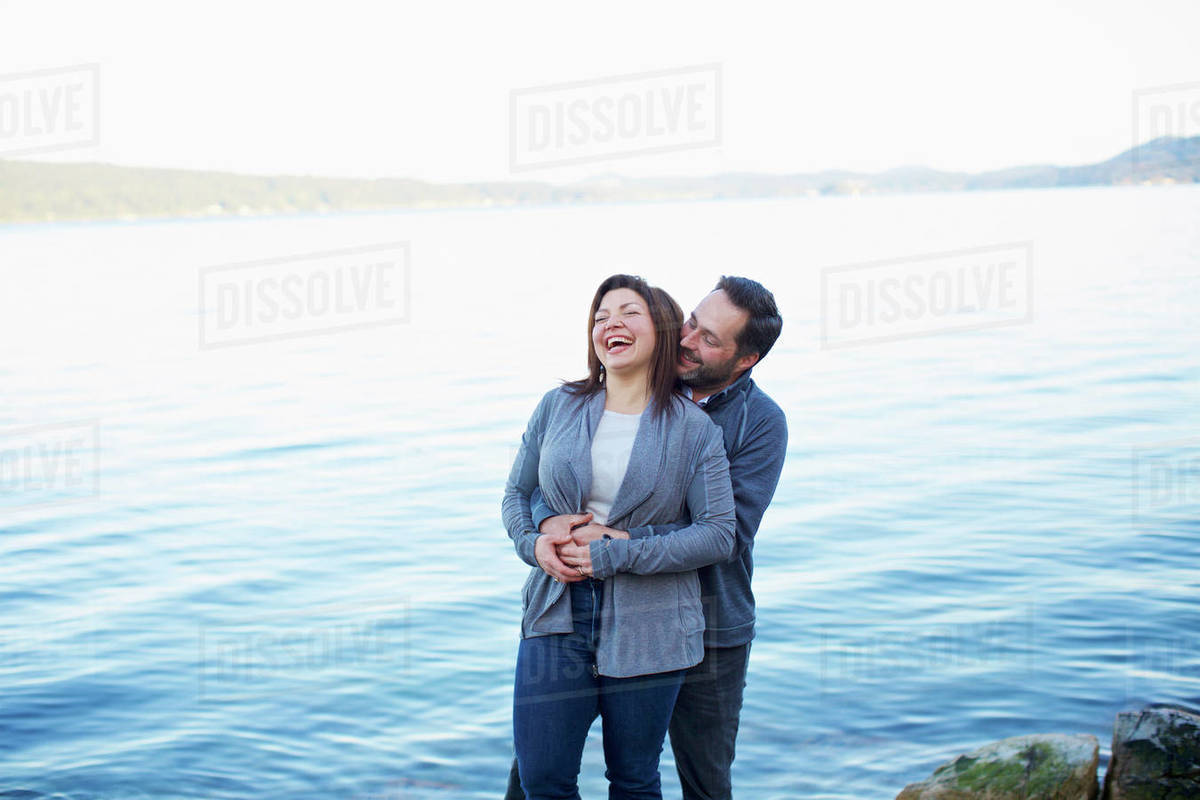 Happy, affectionate couple laughing and hugging at lake Royalty-free stock photo