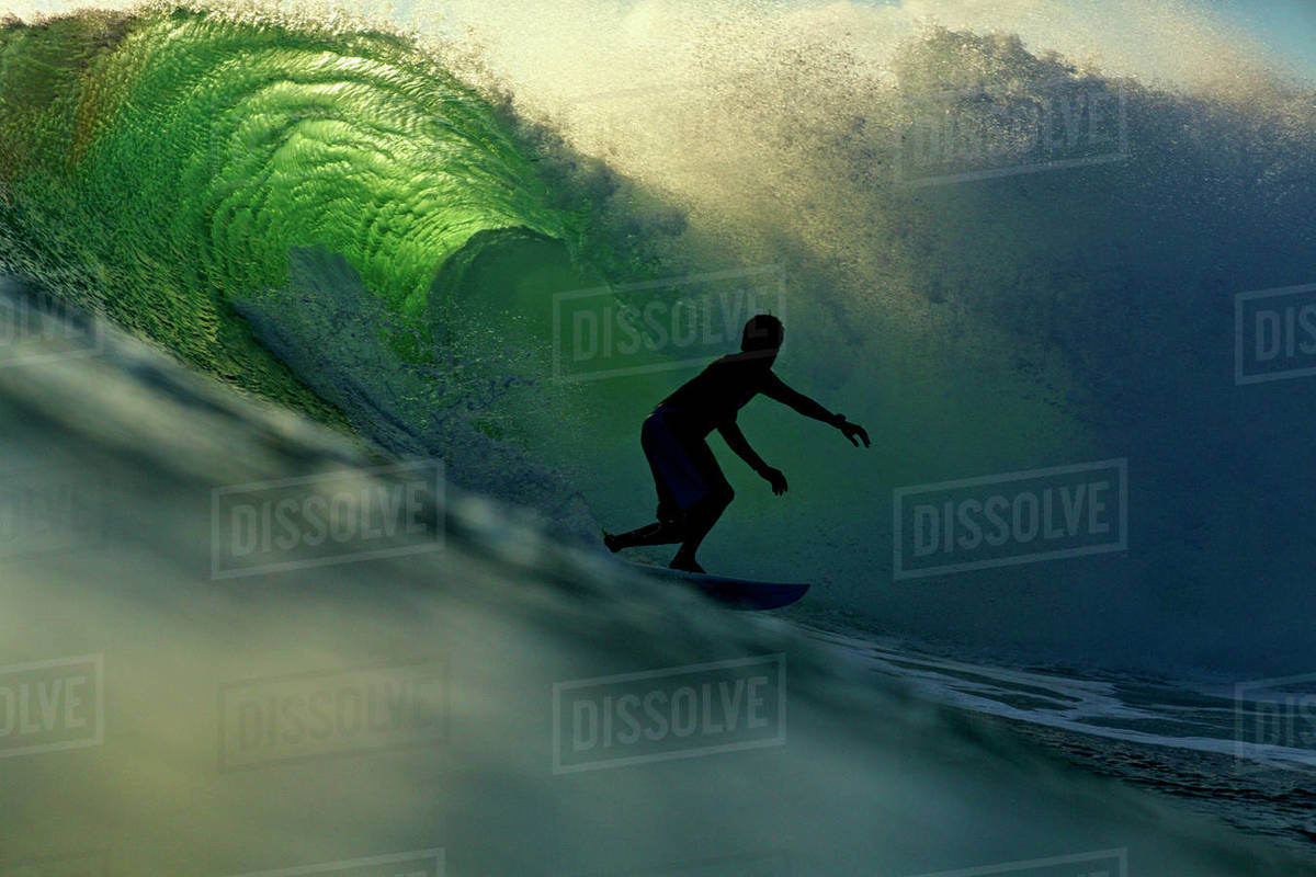 Silhouetted male surfer riding ocean Royalty-free stock photo