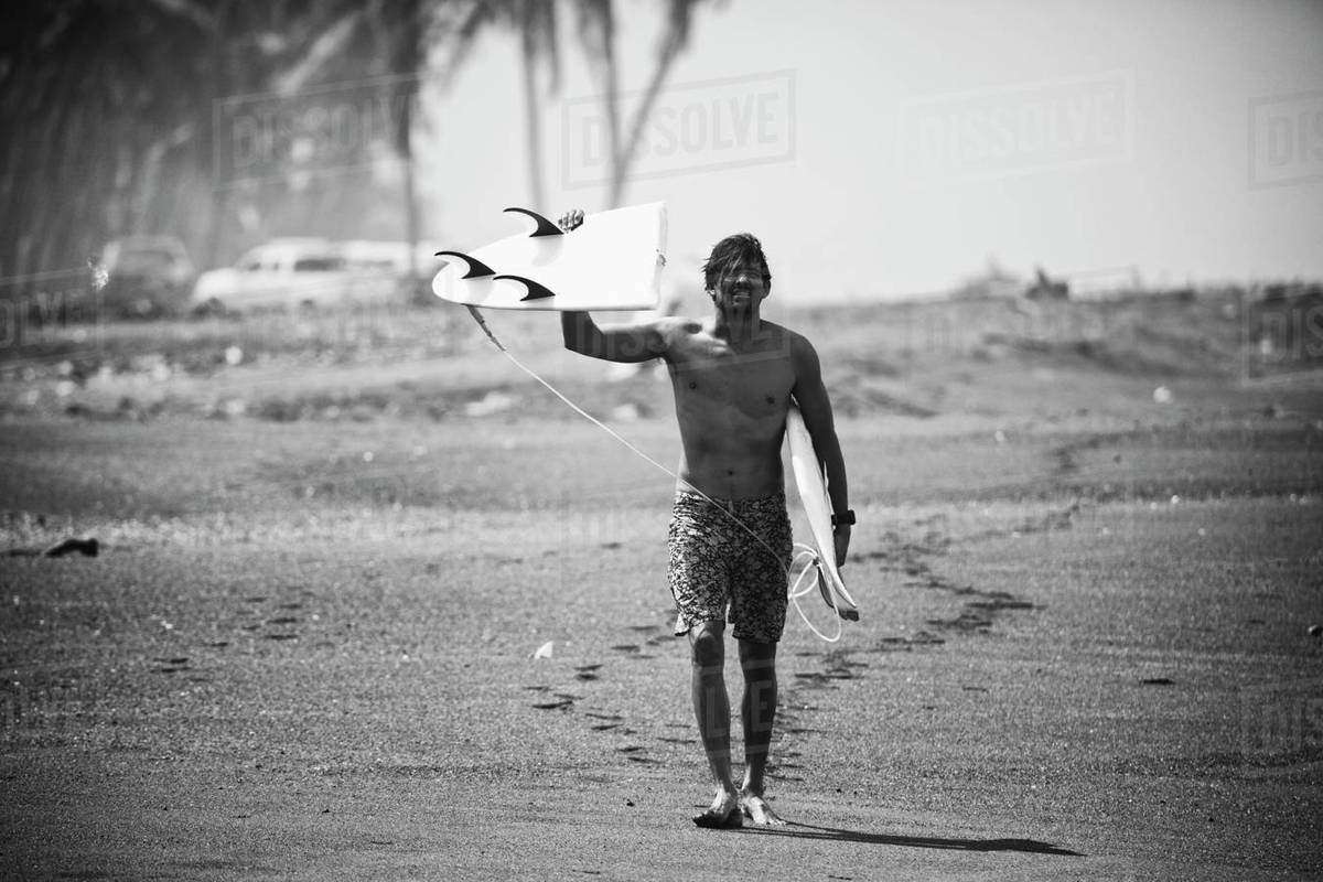 Portrait male surfer holding broken surfboard on beach Royalty-free stock photo