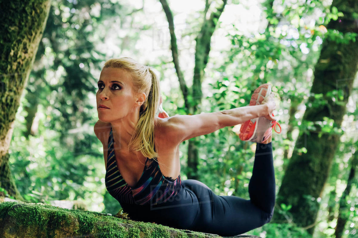 Focused, fit female personal trainer stretching in forest Royalty-free stock photo