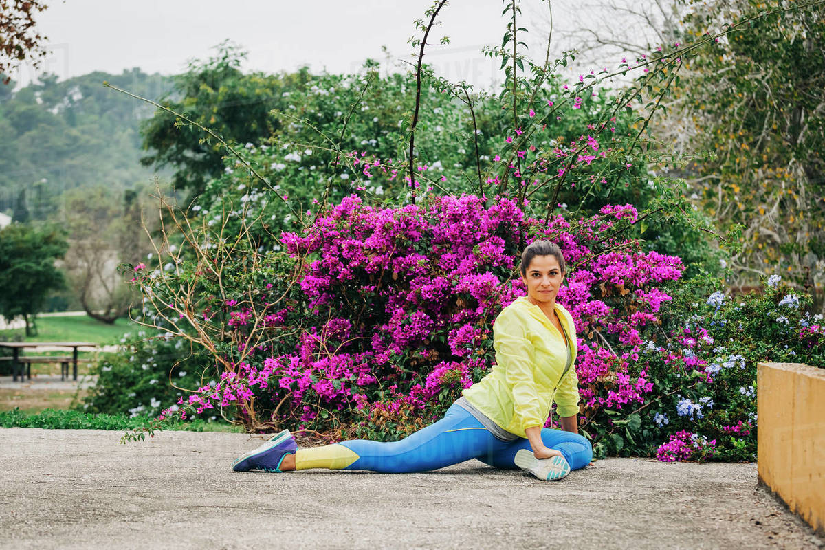 Portrait fit female personal trainer exercising, stretching in park Royalty-free stock photo
