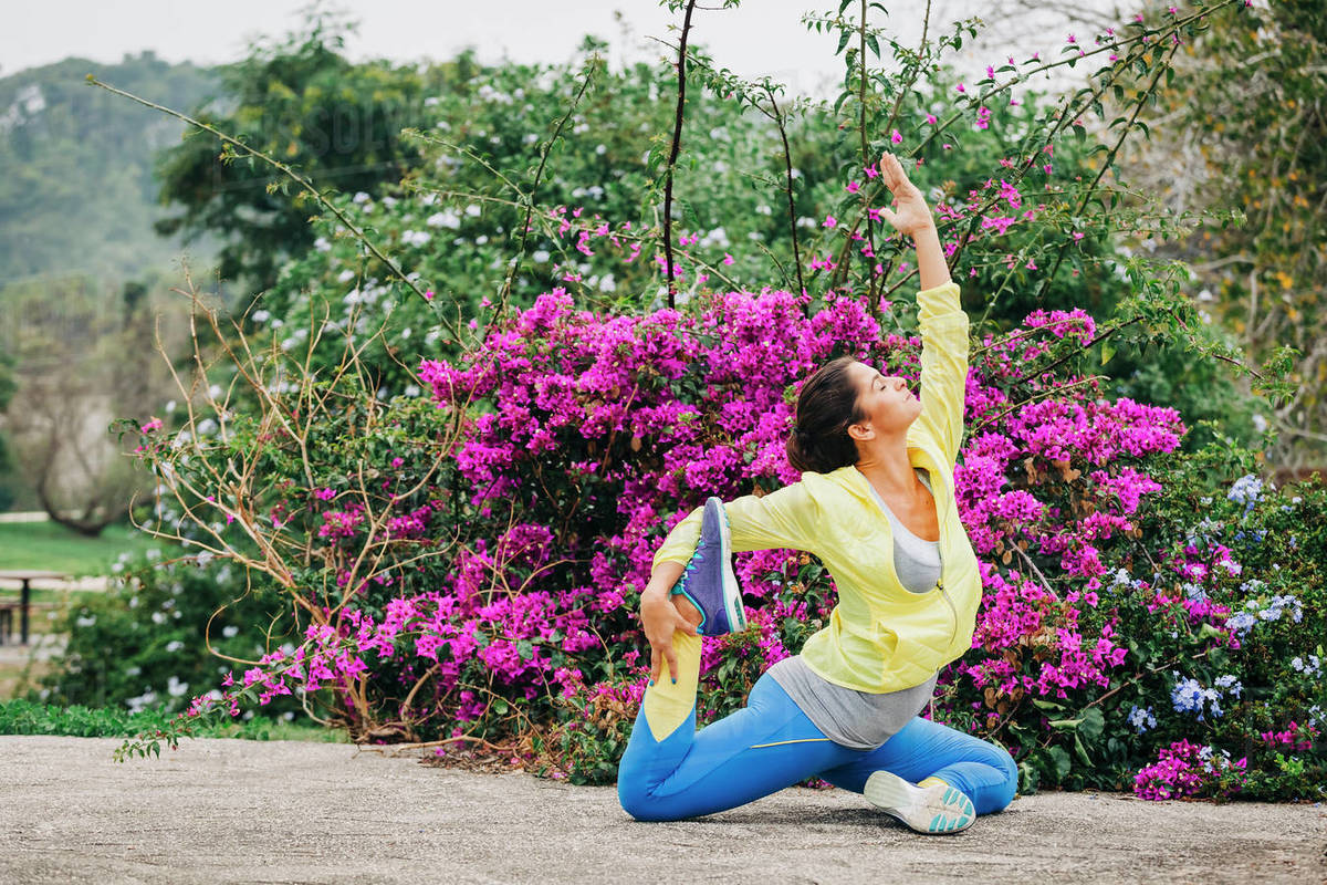 Fit female personal trainer exercising, stretching in park Royalty-free stock photo