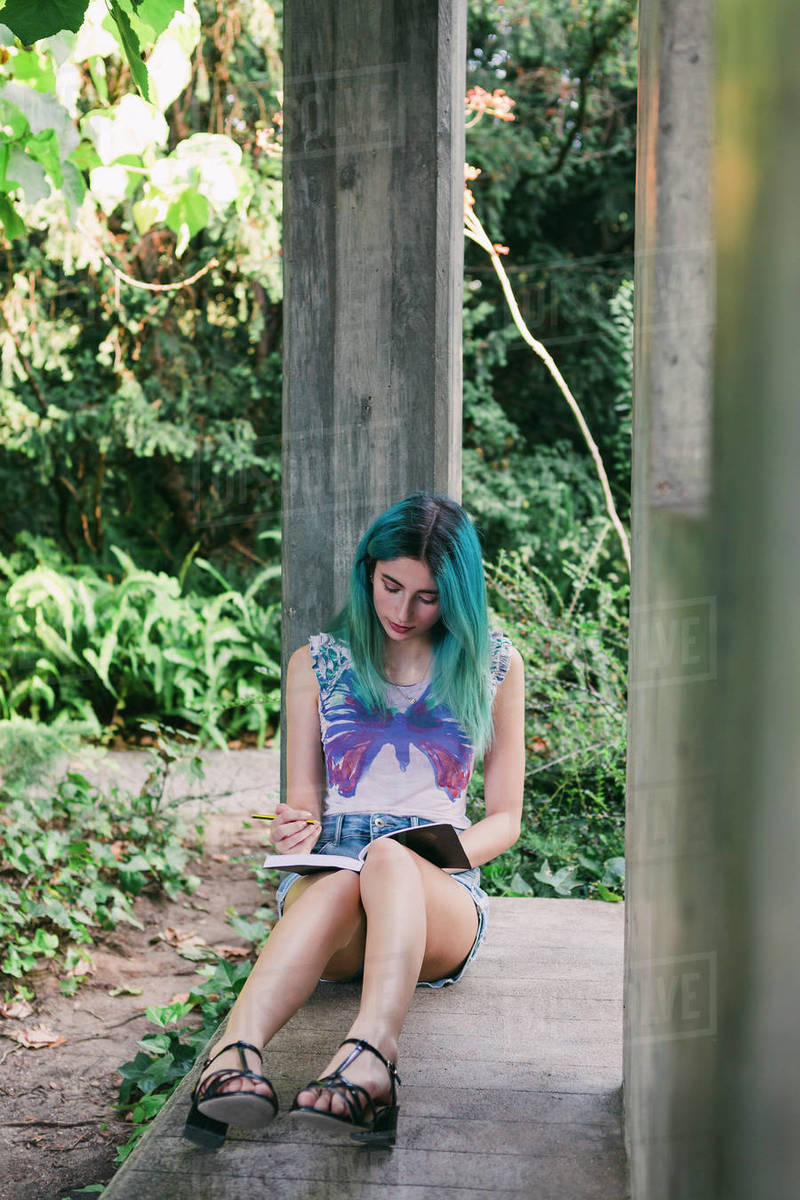 Young woman writing in journal in park Royalty-free stock photo