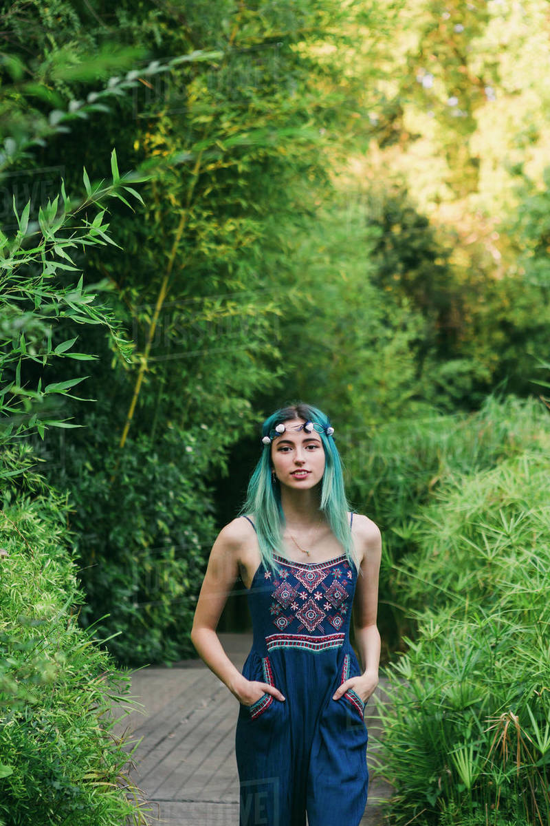 Portrait young woman with blue hair on footpath in lush park Royalty-free stock photo