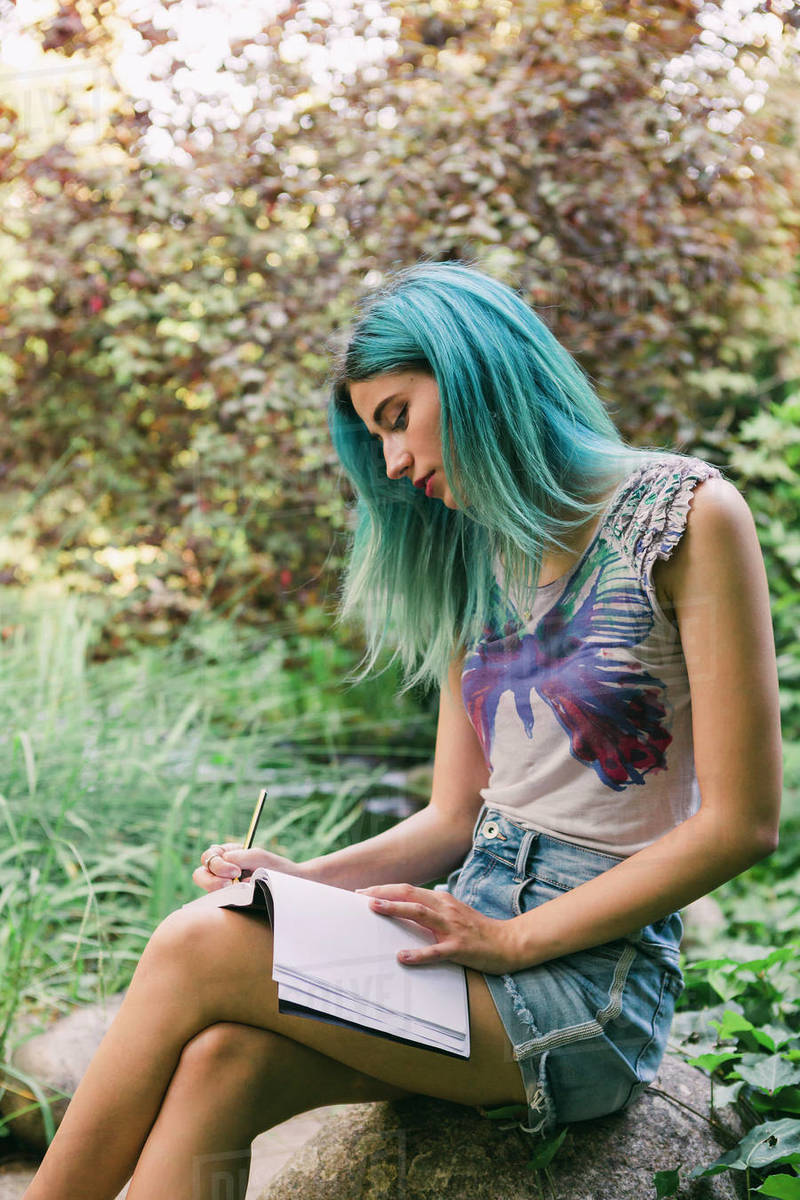 Young woman with blue hair writing in journal in park Royalty-free stock photo