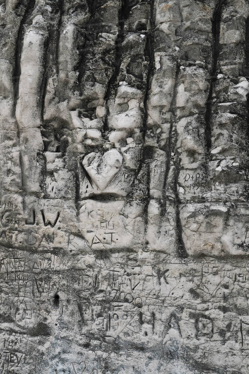 Initials and heart-shape carved into rock Royalty-free stock photo