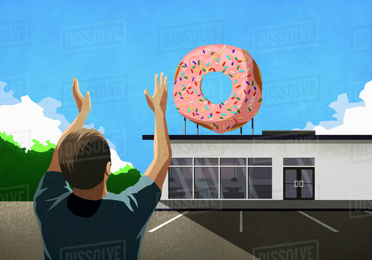 Man with arms raised looking up at pink donut on top of bakery Royalty-free stock photo