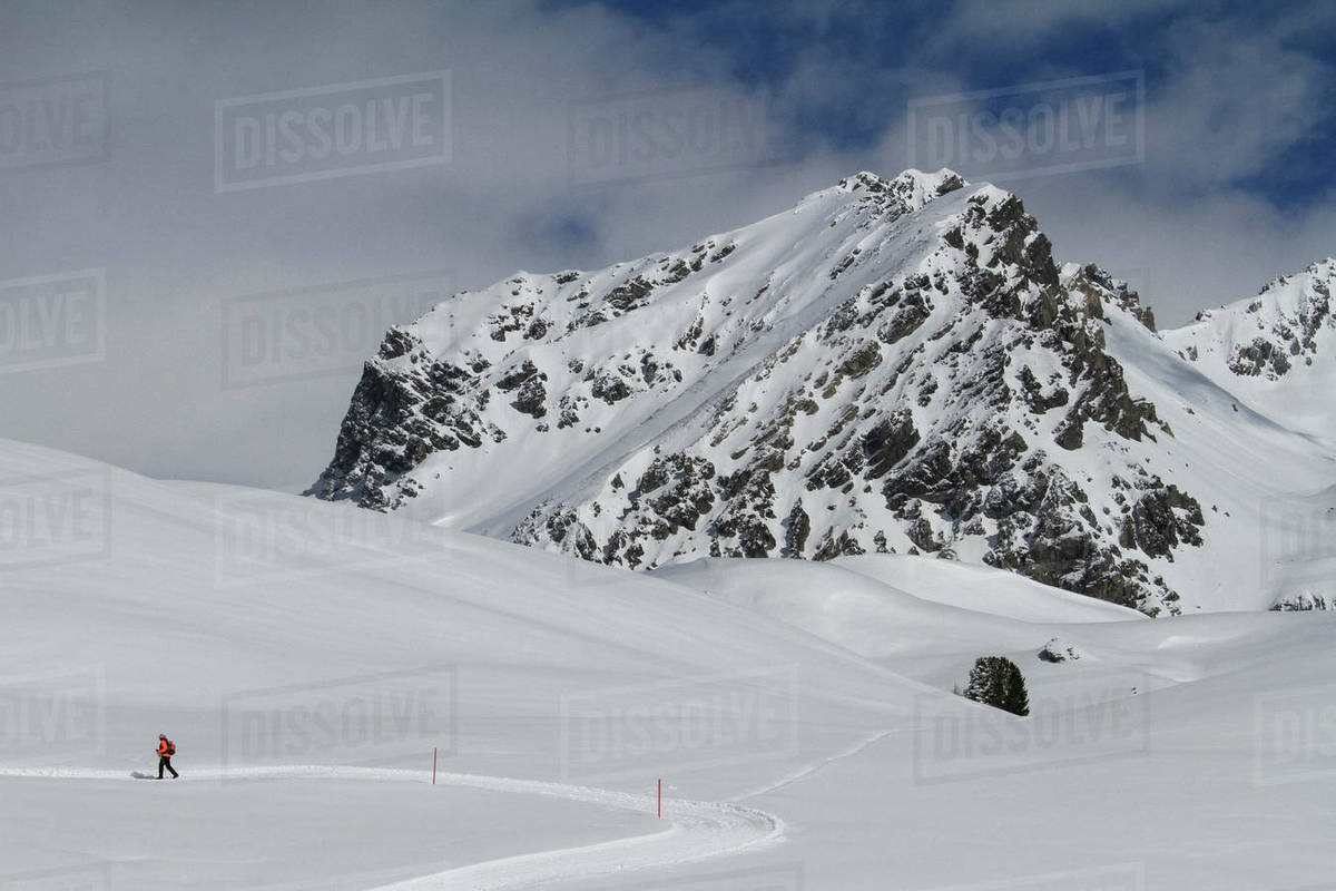 Snowshoer on sunny snowy mountain, Minschuns, Canton of Grisons, Switzerland Royalty-free stock photo
