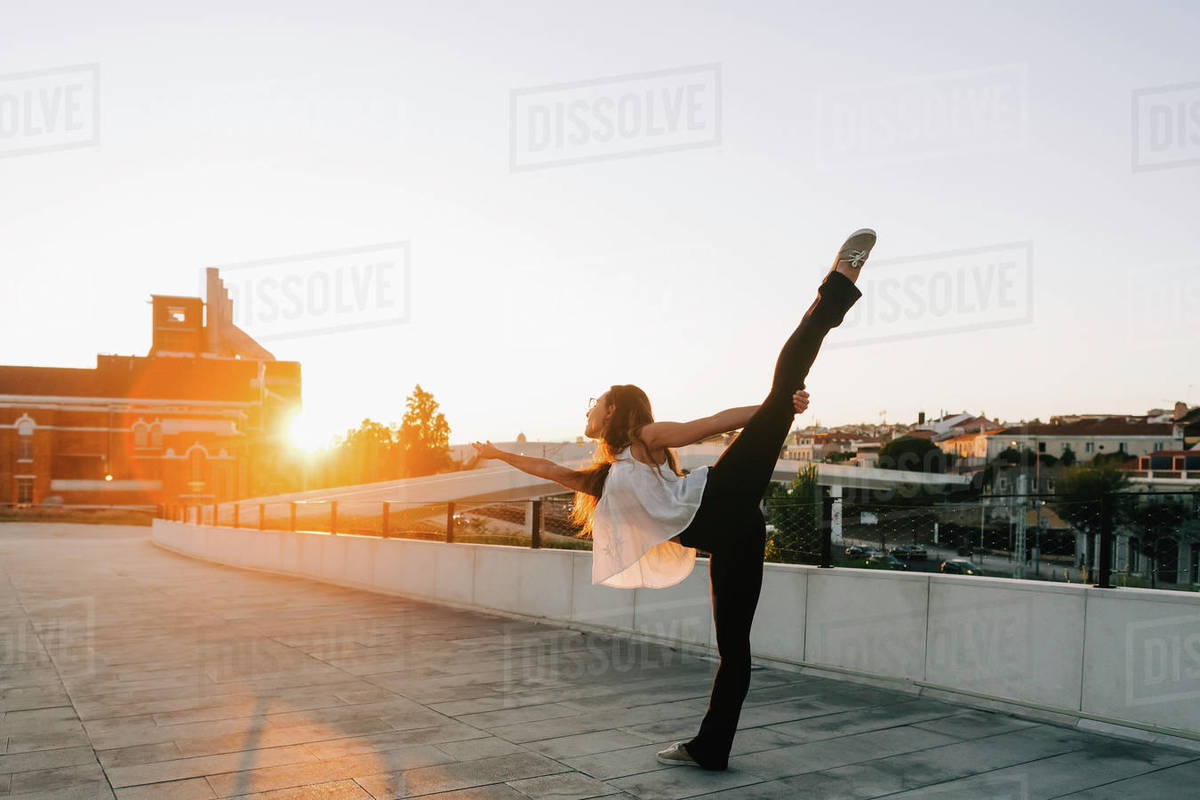 Graceful young female dancer doing standing splits in sunny urban park Royalty-free stock photo