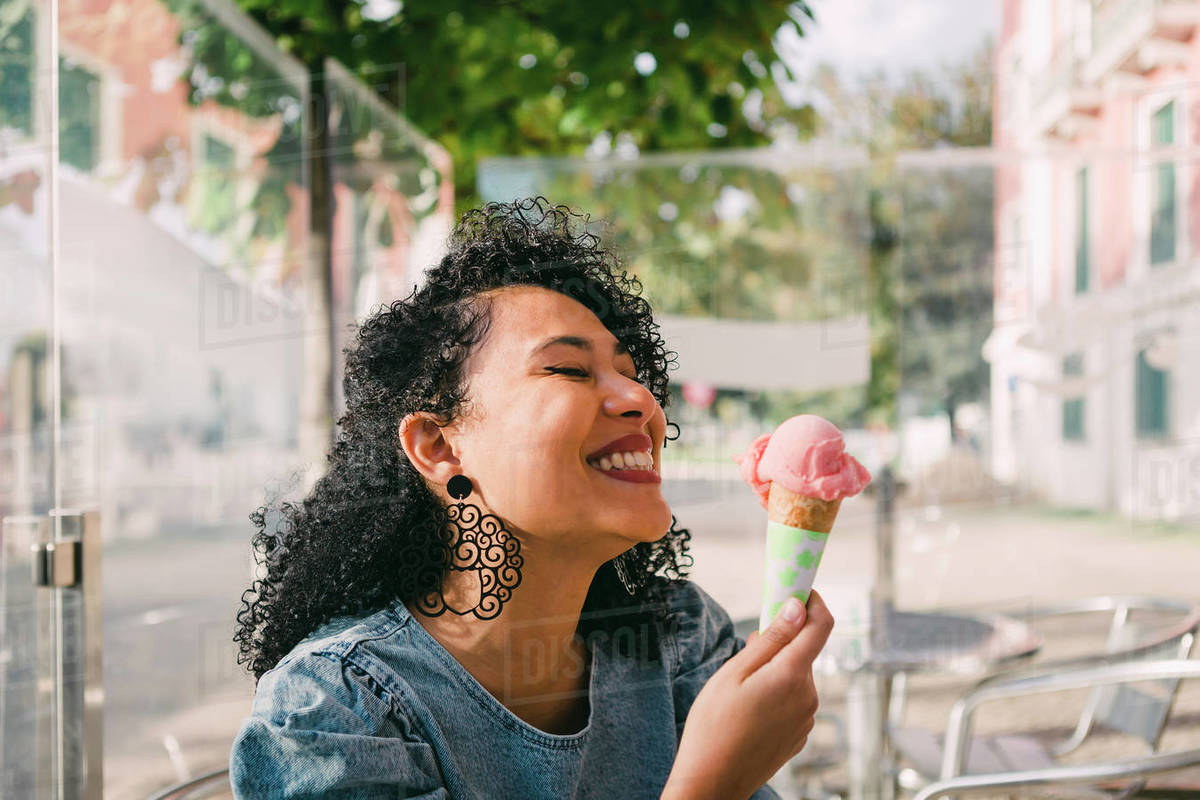 Carefree, excited young woman enjoying pink ice cream cone on sunny cafe patio Royalty-free stock photo